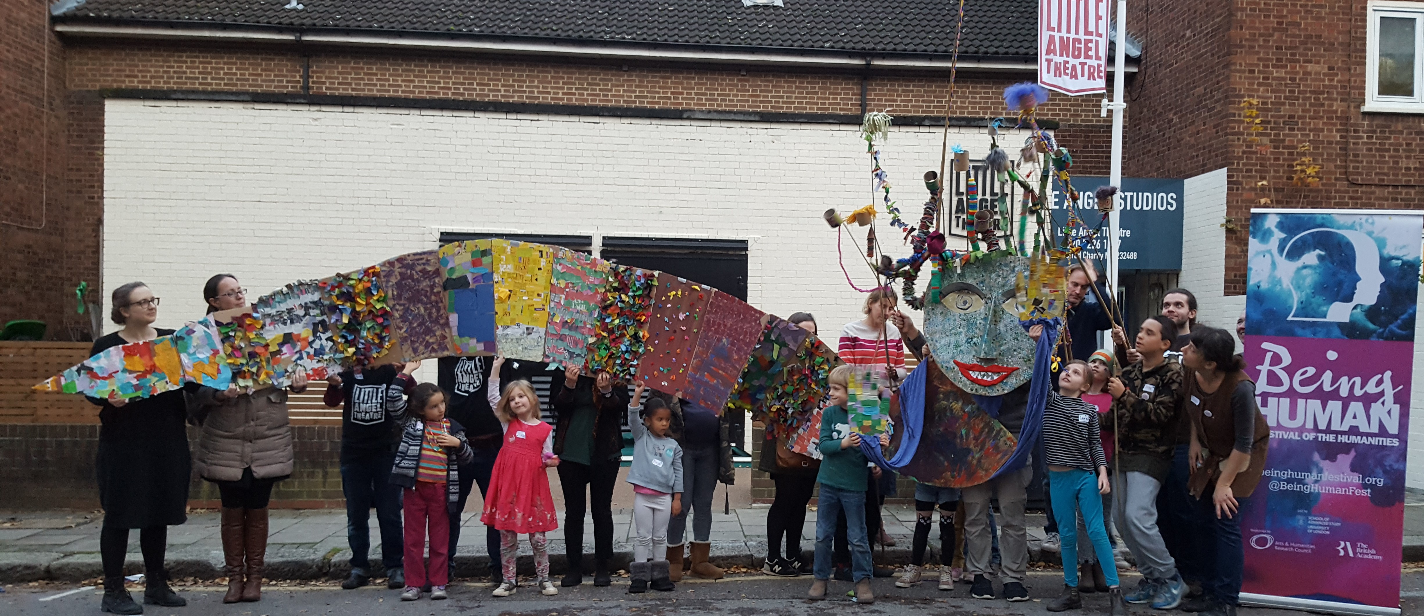A group of adults and children hold up a giant puppet made of card and fabric. The puppet has a long snake-like body and a large head with snakes for hair. Two signs are visible in the picture. One reads 'Little Angel Theatre'; the other reads 'Being Human: festival of the humanities'.